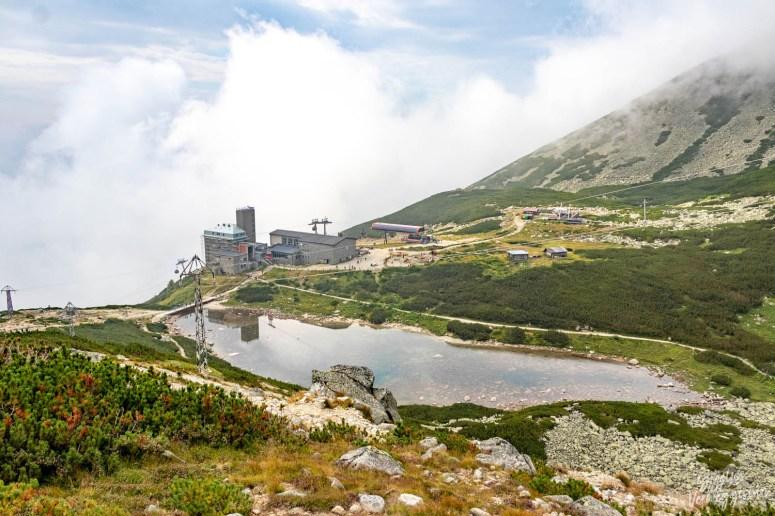 Het liftstation van Skalnaté pleso met het meer ervoor en wolken op de achtergrond.