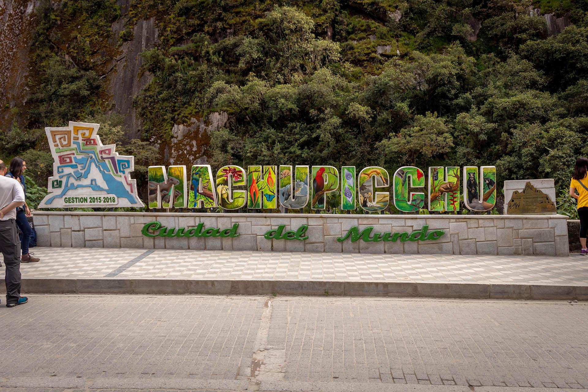 Welkomstbord in Aguas Calientes met grote gekleurde letters.