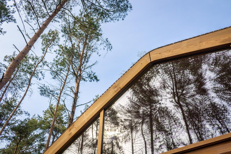 Weerspiegeling van de bomen in het bos in het bovenste driehoekige raam van de Cabiner