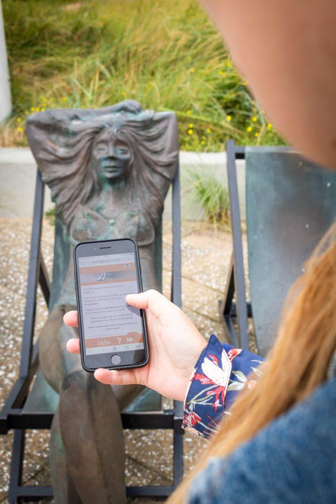 Manouk houdt een telefoon omhoog met de Schipseljagd in Katwijk voor een beeld van een zonnende vrouw