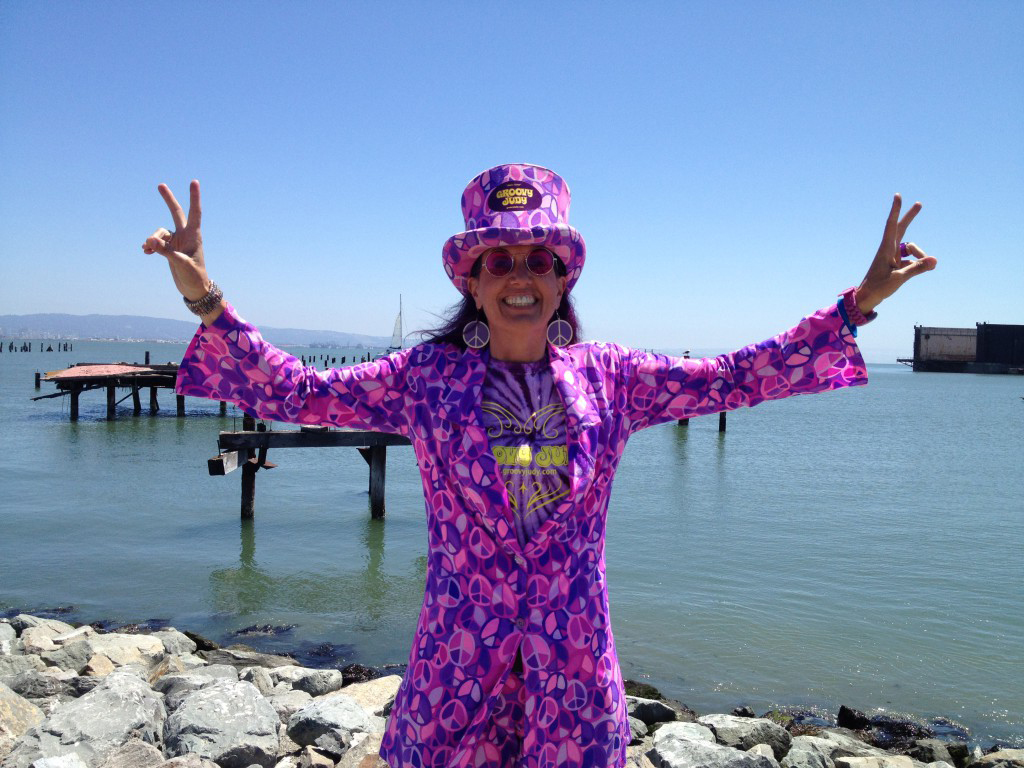 Judy flashes the peace sign at the San Francisco Marathon in front of the bay
