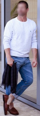 Man in white polo, schlubby jeans, and brown suede slippers