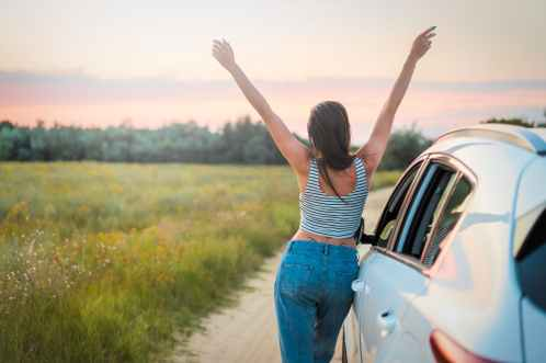 "Alt=""Millennial woman standing by a car in front of a field with her hands up"""