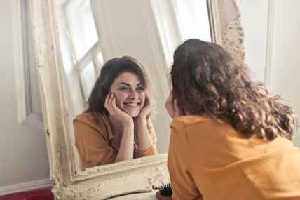 A woman with brown hair who is practicing self-compassion by smiling at herself in the mirror