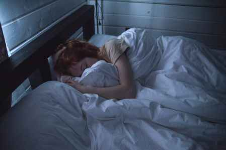 Woman with red hair who is staying in bed because she is depressed
