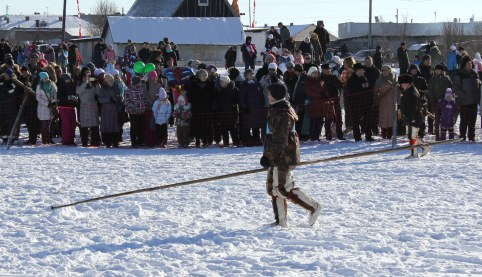 A driver heads to the start line carrying the long pole used to prod the reindeer into action.
