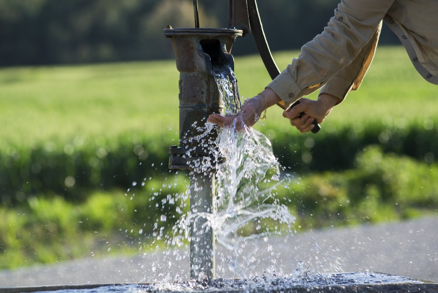 Hands pumping water from a well.