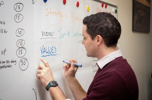 Person writing a list of values on a whiteboard