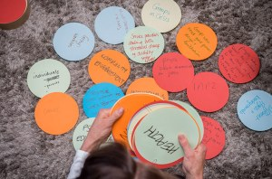Overhead shot of a person placing a series of coloured paper circles down. Circles are labelled with names like 'Health' and 'Community Engagement'
