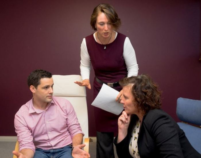 In a meeting room, two seated people, a man and a woman are looking at each other, while another woman stands between them, trying to intervene in their frowning interaction