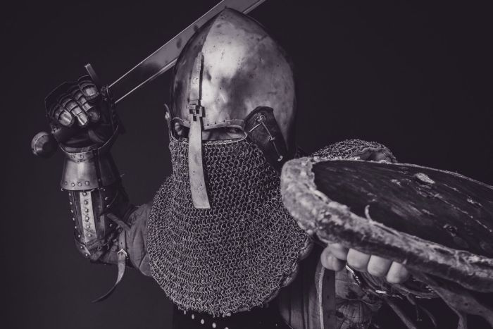 Mediaeval knight in full armour brandishing a sword and shield