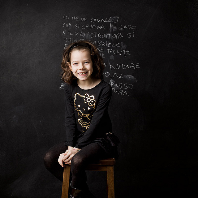 Girl writing in black board in Italian
