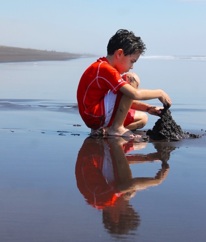 boy playing with sand at black sand beach with reflection in the water