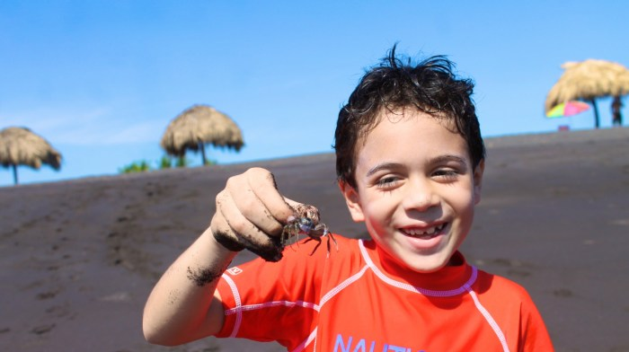 boy with crab at black sand beach in Guatemala