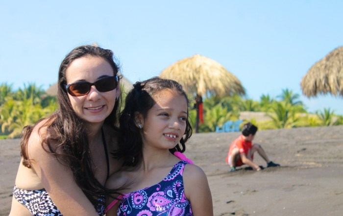 family at a black sand beach in Guatemala's Pacific coast