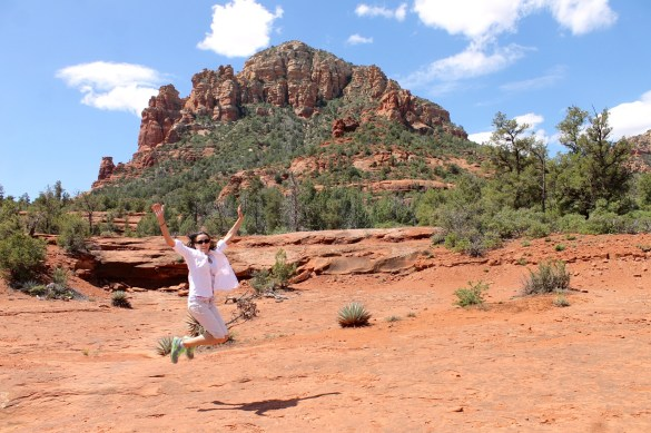 woman hiker jumping for joy in Sedona red rocks