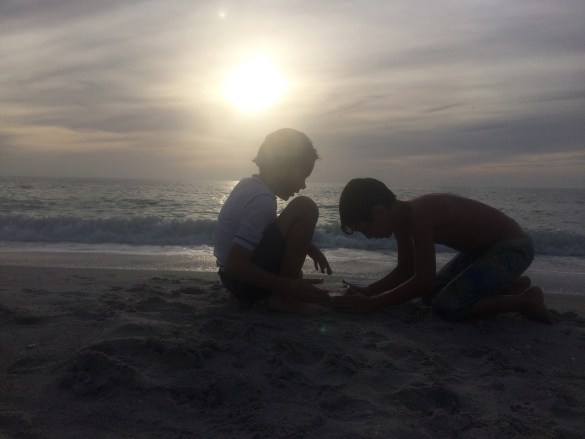 boys playing at the beach during sunset