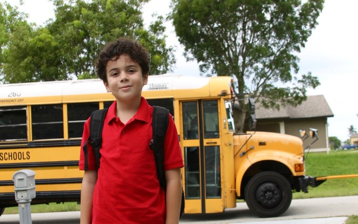 Latino boy in front of bus
