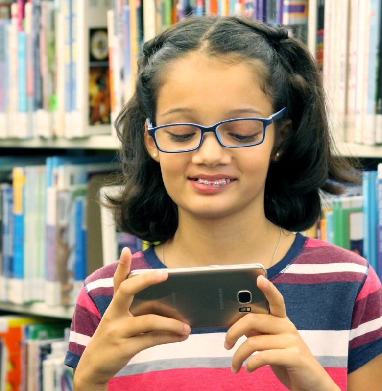 girl with cell phone: Kids first mobile phone