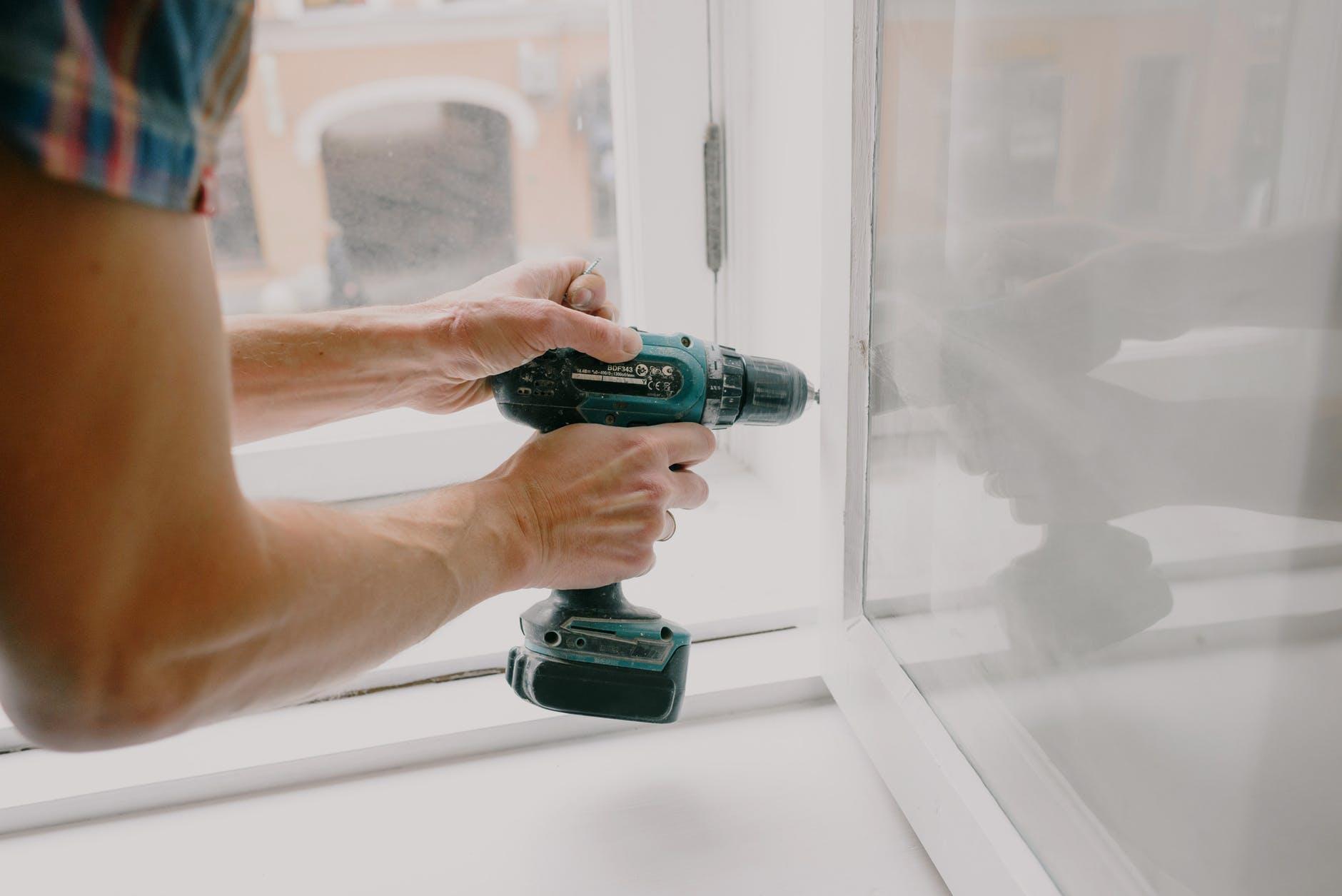 workman screwing window frame during housework