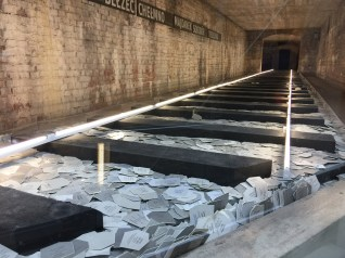 "A memorial installation called ""Tracks"" that lists names and information of known casualties of the Holocaust. Each card represents 6,000 unnamed victims."