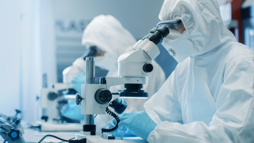 Two,Engineers/,Scientists/,Technicians,In,Sterile,Cleanroom,Suits,Use,Microscopes