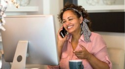woman looking at desktop computer on phone smiling