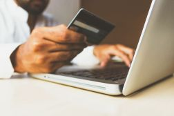 man holding credit card showing online sales