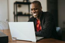man smiling at laptop on desk