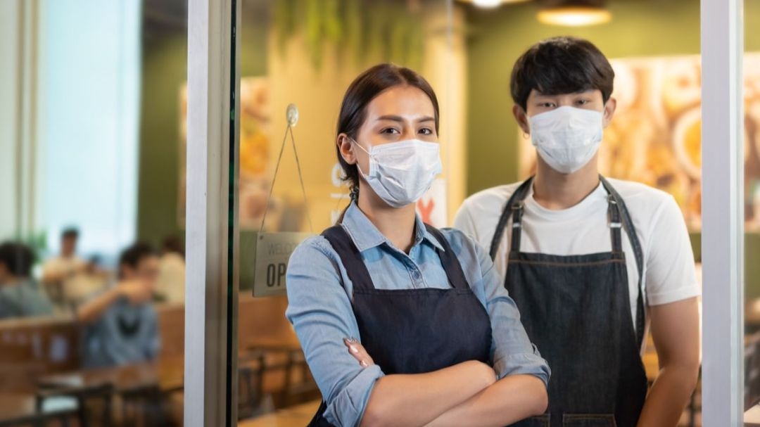 two restaurant owners in masks in front of their store
