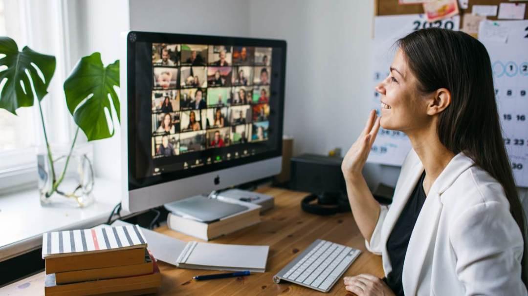 woman in blazer waving at people on computer screen virtual alignable cal