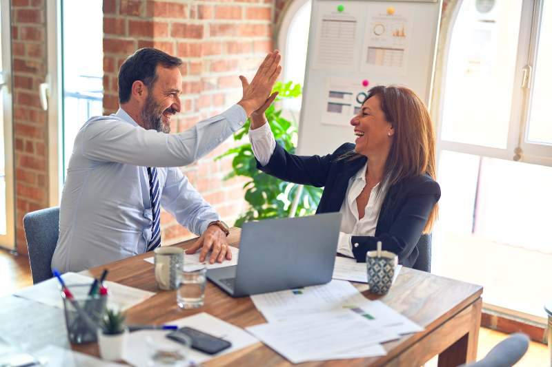 man and woman business owner high fiving after hosting online event