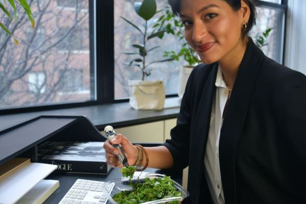 woman eating salad in front of computer smiling |  9 Fun Virtual Event Ideas to Hit Your Business Goals