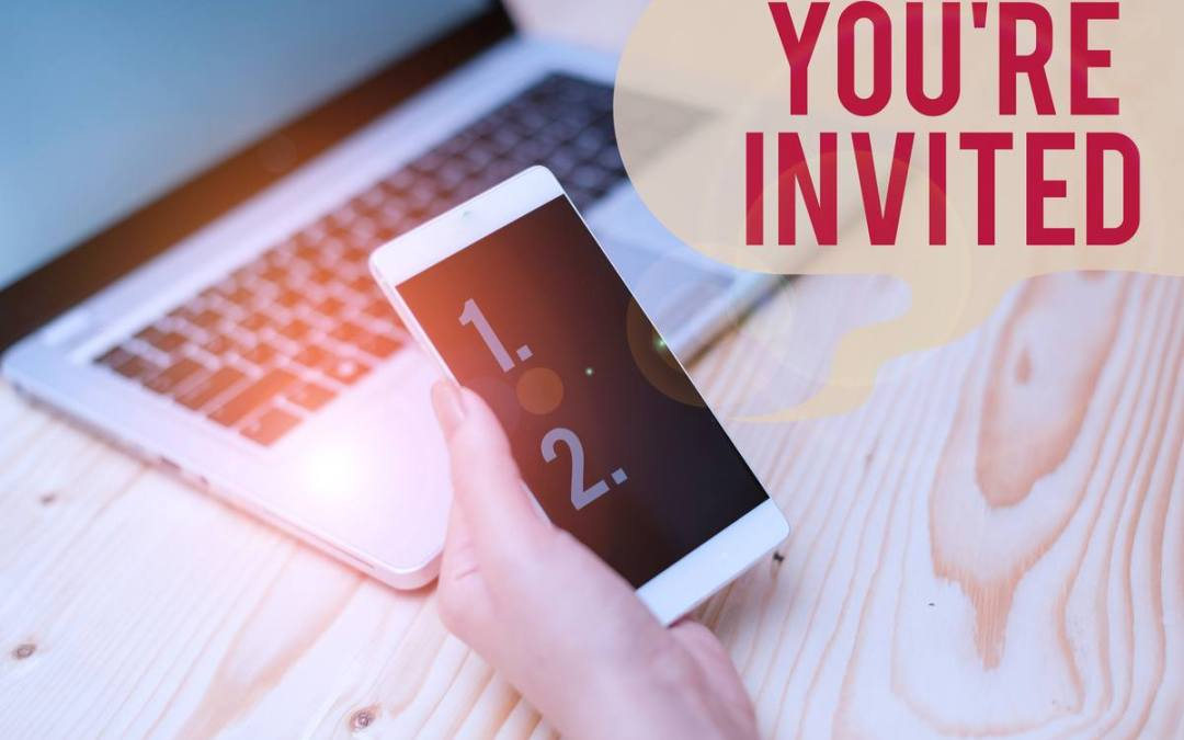 you're invited sign sitting near cell phone and laptop   How to Create Virtual Event Invitations That Wow Attendees