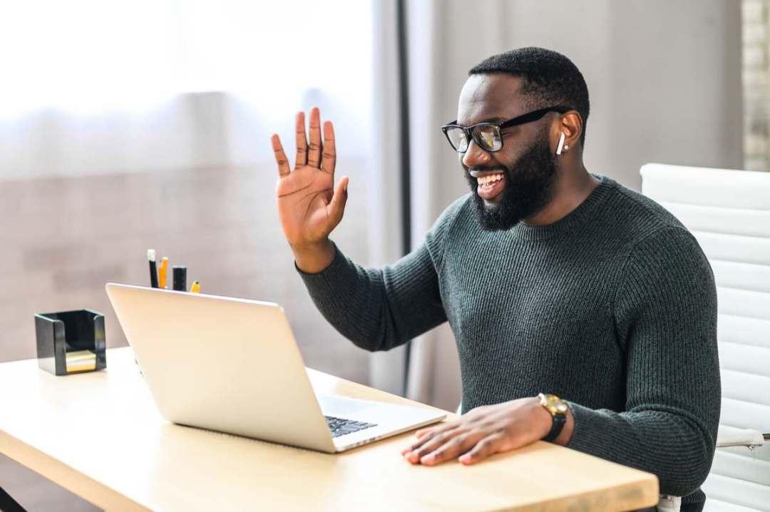 man waving at laptop screen during online meeting