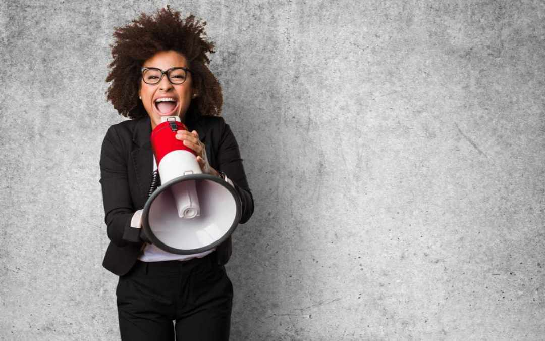 woman in glasses screaming into red megaphone