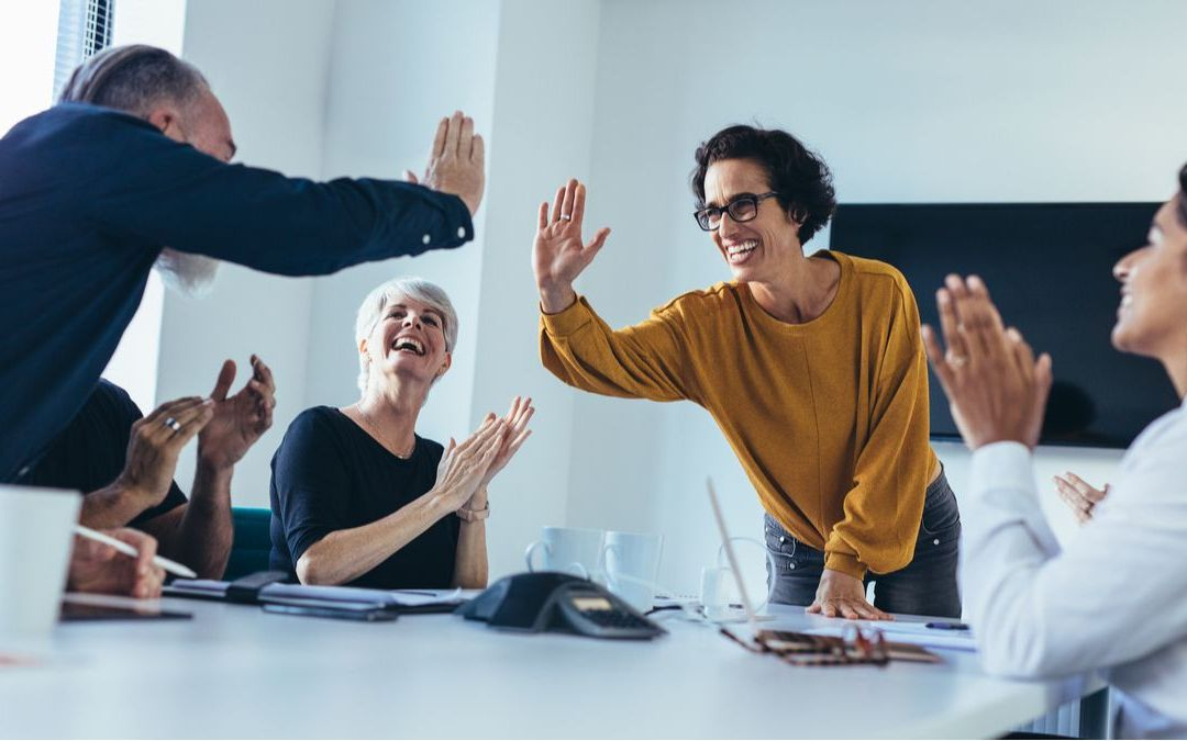 diverse group of people high fiving in office setting