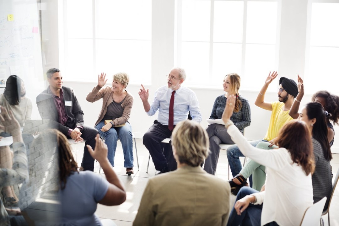 diverse group of people networking raising hands in a circle