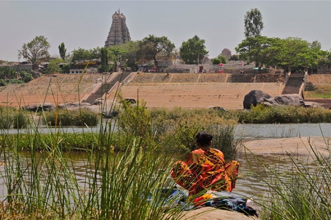 hampi river india, Indian woman washing clothes in the river