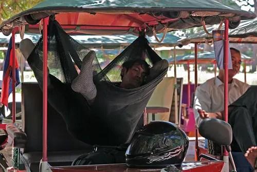 cambodian tuk-tuk driver relaxes
