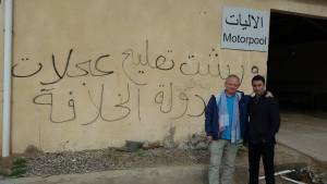 """The Iraqi Army base auto repair shop. During the ISIS assault three weeks before, a fighter sprayed graffiti which Samir translates as, """"Only for cars of the Islamic State."""" Most ISIS attackers were later killed by a U.S. airstrike."""