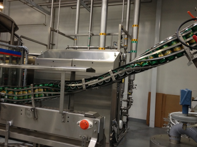 Empty Torpedo cans move through the canning line.
