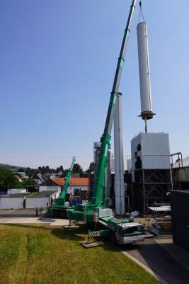 Autokran hebt Schornstein vom Turbinen-Gebäude