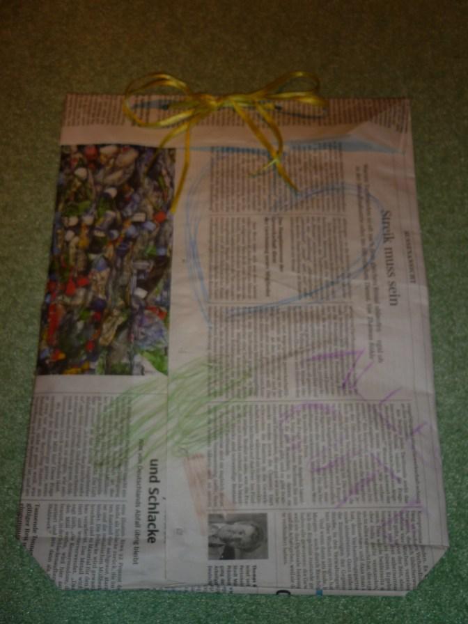 Durch die Löcher wird ein Band gezogen und zu einer Schleife gebunden :) Fertig ist die Geschenktüte! Zugegeben, die Verzierungen könnten kunstvoller sein, aber es ist ein Anfang ;)