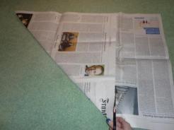 Für die Mülltüte werden zwei oder drei Lagen Zeitungspapier aufeinandergelegt und zu einem Quadrat geschnitten.