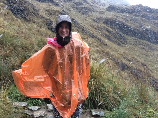 Beth giving a fake smile in the middle of a winter storm - Inca Trail right after Dead Woman's Pass