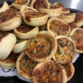 A plate piled high with mixed mini-quiches.