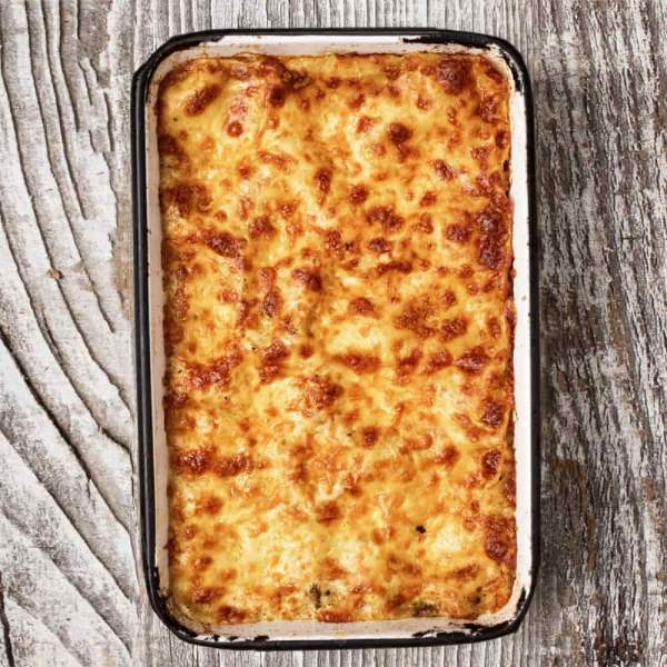You are looking at a golden brown lasagne in a tin baking dish on a wooden counter.
