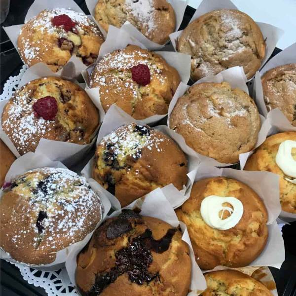 A plate with a dozen fresh baked muffins with different toppings of raspberries or icing sugar.