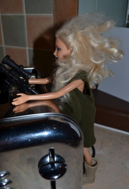 Barbie rocking the Action Man onesie and desert boots. And big assault rifle